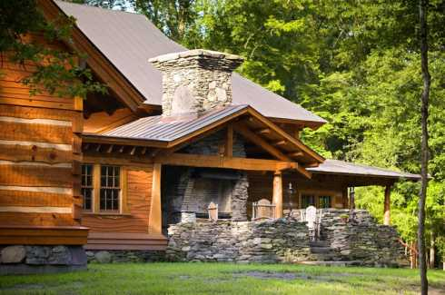 fireplace and chimney graces the back of this log cabin home plan